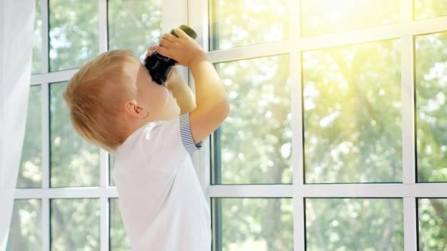 Widok z boku małego chłopca trzymającego czarną lornetkę i odwracającego wzrok w oknie eksplorującym przyrodę