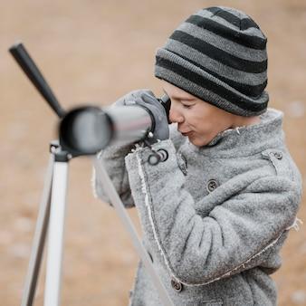 Widok z boku małego chłopca za pomocą teleskopu