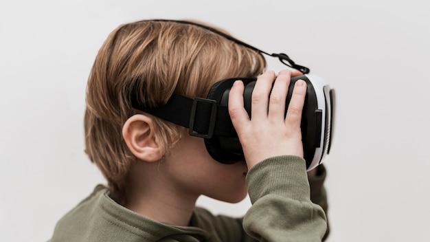 Widok z boku małego chłopca za pomocą zestawu słuchawkowego wirtualnej rzeczywistości