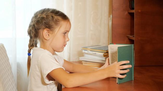 Widok z boku małej dziewczynki z warkoczami siedzącej przy stole i czytającej podręcznik odrabiania lekcji