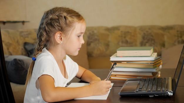 Widok z boku małej dziewczynki z warkoczami siedzącej przy stole ze stosem książek, oglądającej laptopa i odrabiającej pracę domową