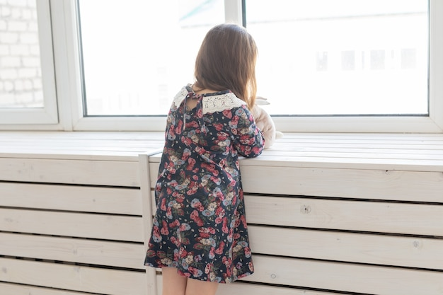 Widok z boku małej niezidentyfikowanej dziewczynki w długiej kwiatowej sukience trzymającej w sobie ulubioną zabawkę króliczka