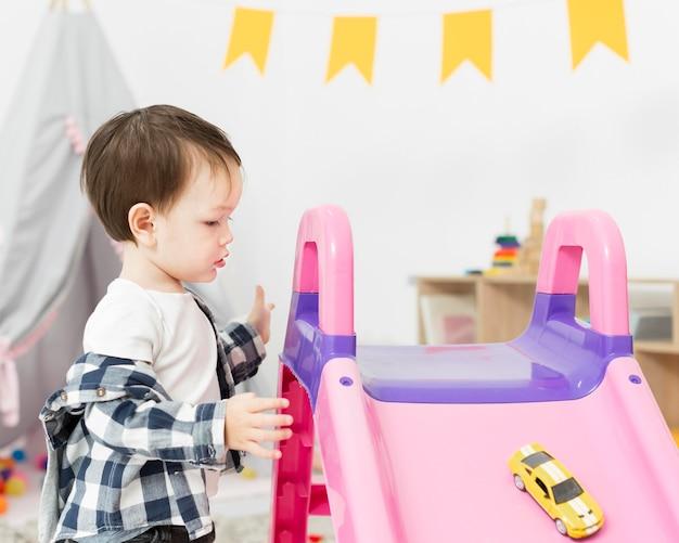 Widok z boku malucha z zabawką i zjeżdżalnią