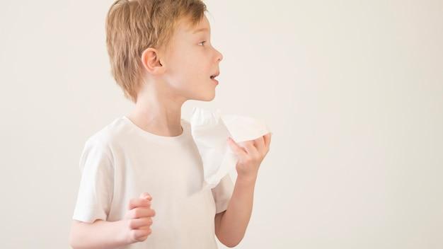 Widok z boku mały chłopiec dmuchanie nosa