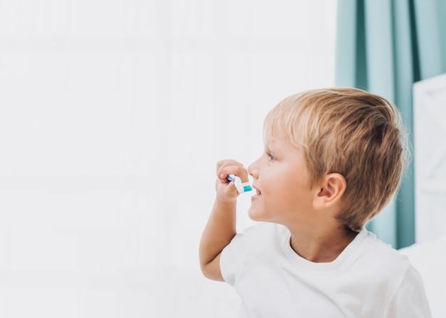 Widok z boku mały chłopiec szczotkuje zęby