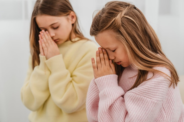 Widok z boku małych dziewczynek modlących się w domu