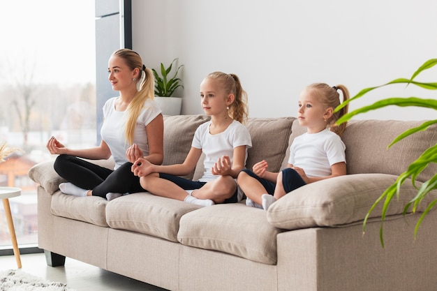 Widok z boku matki córki medytuje w domu na kanapie