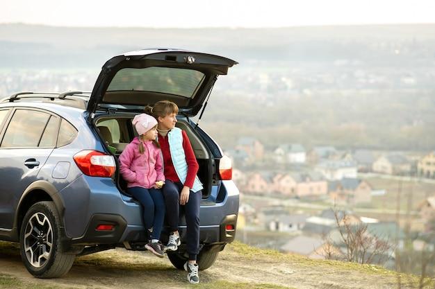 Widok z boku matki z córką, siedząc w bagażniku samochodu i patrząc na naturę. koncepcja odpoczynku z rodziną na świeżym powietrzu.
