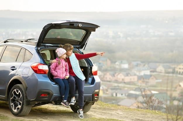 Widok z boku matki z córką, siedząc w bagażniku samochodu i patrząc na naturę.