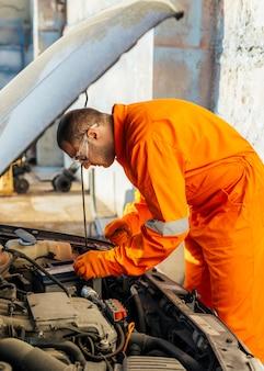 Widok z boku mechanika w okularach ochronnych i mundurze