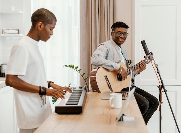 Widok z boku męskich muzyków w domu, grających na gitarze i elektrycznej klawiaturze