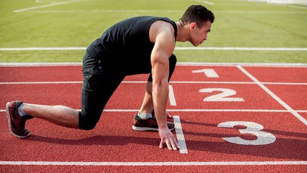 Widok z boku męskiego biegacza sprinter przygotowuje się do rozpoczęcia wyścigu