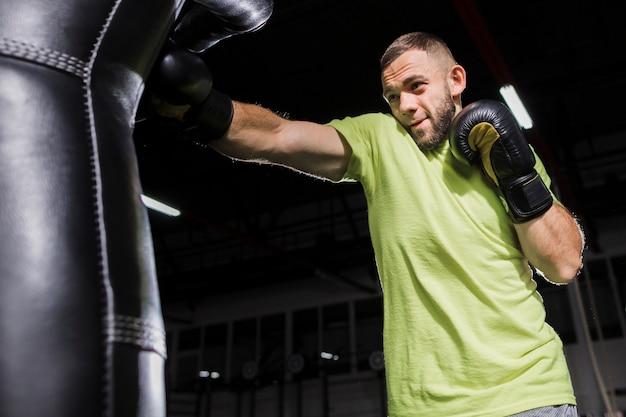 Widok z boku męskiego boksera ćwiczącego z workiem treningowym