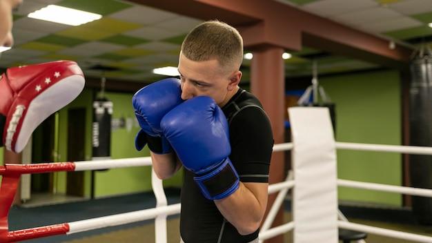Widok z boku męskiego boksera z trenerem i rękawiczkami
