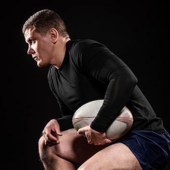 Widok z boku męskiego gracza rugby trzymając piłkę