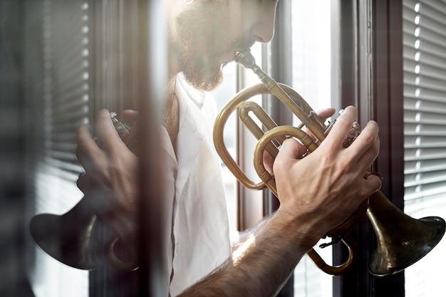 Widok z boku męskiego muzyka grającego na kornecie w oknie