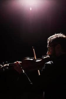 Widok z boku męskiego muzyka grającego na skrzypcach z miejsca na kopię