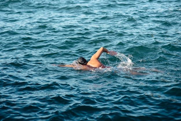 Widok z boku męskiego pływaka pływania w wodzie