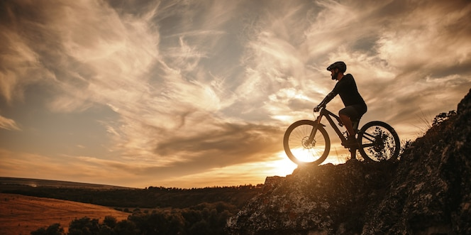 widok z boku męskiego rowerzysty w kasku siedzącego na rowerze górskim przed zachmurzonym niebem o zachodzie słońca na wsi