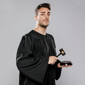 Widok z boku męskiego sędziego z młotkiem