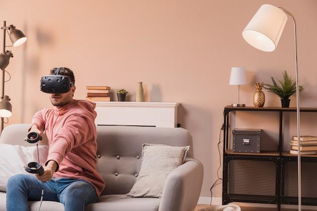 Widok z boku mężczyzna gra z wirtualnym zestawem słuchawkowym