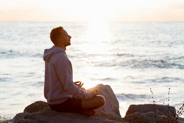 Widok z boku mężczyzna medytuje na plaży