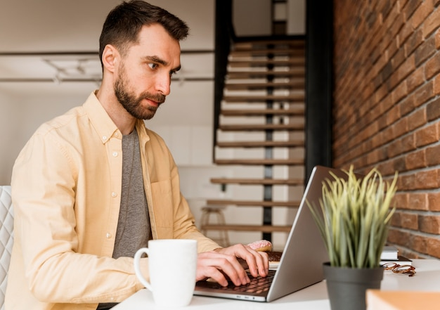 Widok z boku mężczyzna o rozmowie wideo na laptopie