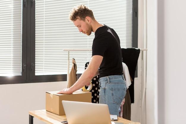 Widok z boku mężczyzna pakuje pudełko