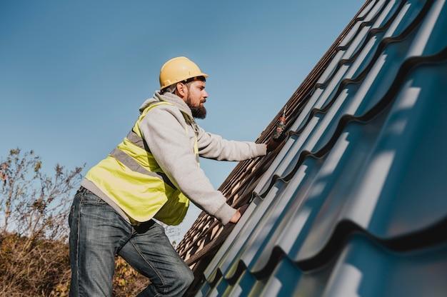 Widok z boku mężczyzna pracujący na dachu