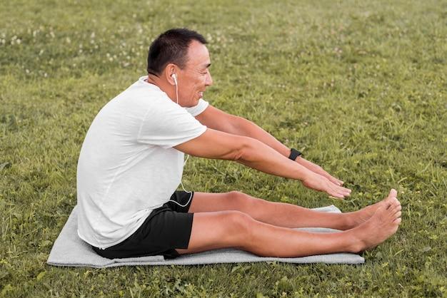 Widok z boku mężczyzna rozciągający się na trawie