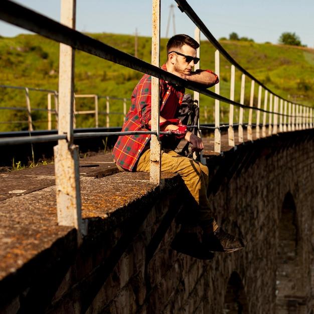 Widok z boku mężczyzna siedzący na krawędzi mostu