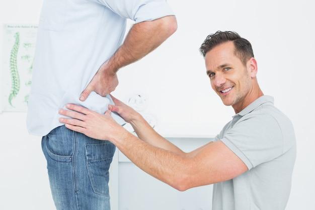 Widok z boku mężczyzny fizjoterapeuty, badając mans z powrotem