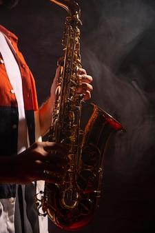 Widok z boku mężczyzny grającego na saksofonie w świetle reflektorów