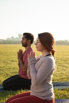 Widok z boku mężczyzny i kobiety medytujących na zewnątrz na matach do jogi
