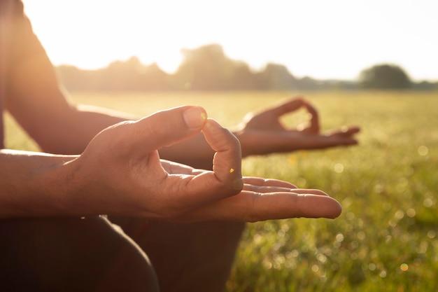 Widok z boku mężczyzny medytującego na zewnątrz