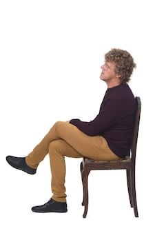 Widok z boku mężczyzny siedzącego na białym tle ze skrzyżowanymi nogami