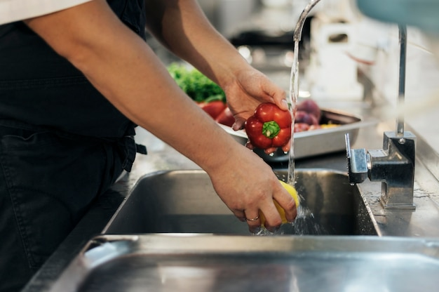 Widok z boku mężczyzny szefa kuchni mycia warzyw