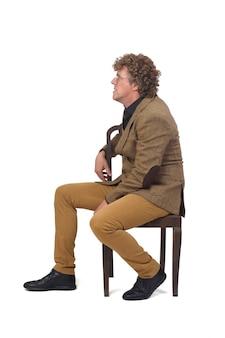 Widok z boku mężczyzny w średnim wieku z marynarką, siedząc na krześle na białym tle