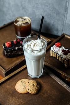 Widok z boku milkshake z bitą śmietaną w szklance z ciasteczkami na tacy