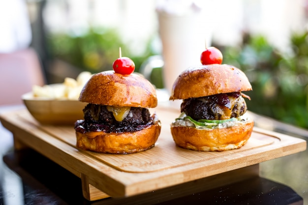 Widok z boku mini burgery z pasztecikiem wołowym z grillowaną cebulą i ogórkiem