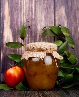 Widok z boku miodu w szklanym słoju i świeżej dojrzałej nektaryny z zielonymi liśćmi na rustykalnej drewnianej ścianie