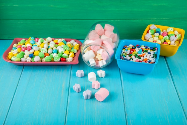 Widok z boku misek z różnymi kolorowymi cukierkami i pianką rozrzuconą ze szklanego słoika na niebieskim tle