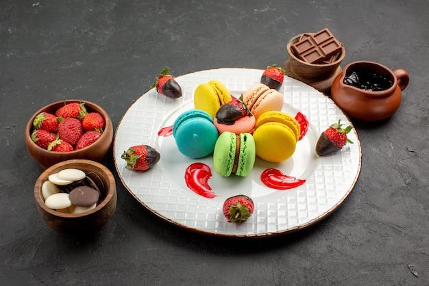Widok z boku miski deserowe z czekoladowymi truskawkami obok talerza apetycznych francuskich makaroników i truskawek na stole