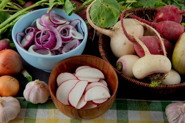Widok z boku miski i kosz warzyw jako rzodkiewka cebula i czosnek na powierzchni tkaniny