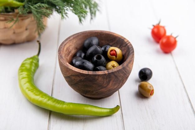 Widok z boku miski oliwek z papryką i koperkiem na powierzchni drewnianych
