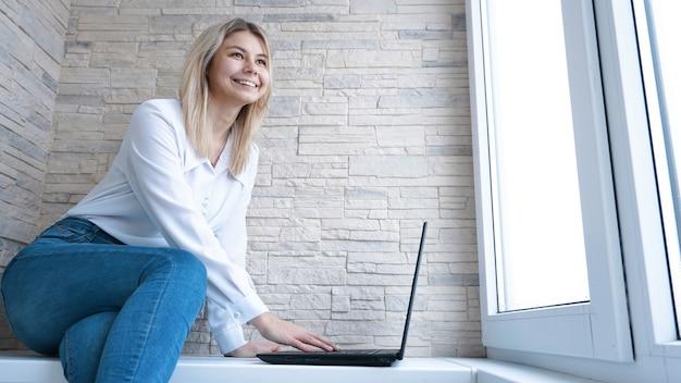Widok z boku. młoda biznesowa kobieta siedzi i robi notatki w notatniku. student uczy się online. blogger z laptopem.