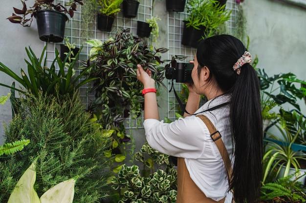 Widok z boku, młoda kobieta ogrodniczka używa aparatu cyfrowego, robi zdjęcie z piękną rośliną doniczkową