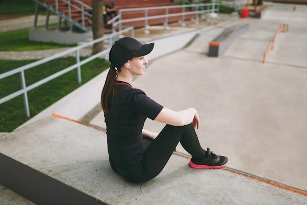 Widok z boku młoda wysportowana brunetka kobieta w czarnym mundurze i czapce ze słuchawkami, słuchając muzyki, odpoczywając i siedząc przed lub po bieganiu, trenując w parku miejskim na zewnątrz