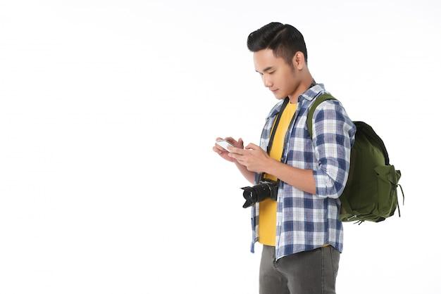 Widok z boku młodego azjatyckiego turysty z plecakiem za pomocą smartfona
