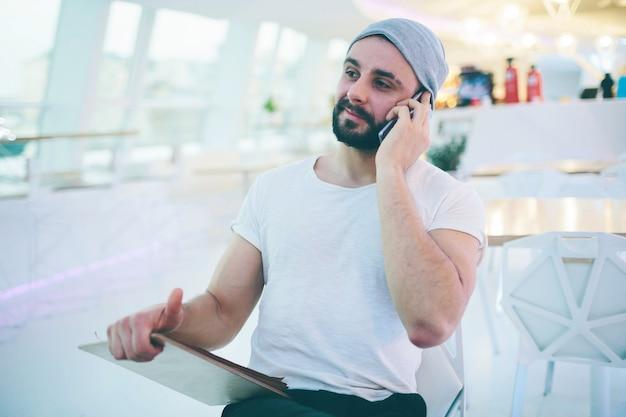 Widok z boku młodego brodatego mężczyzny, ubranego w szary kardigan, siedzącego przy okrągłym drewnianym stole w kawiarni z nowoczesnym wnętrzem i trzyma smartfona